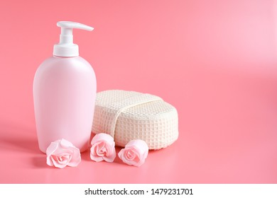 Pink plastic bottle for liquid soap  or cosmetique with pink rose flower beside and sponge for shower on pink background