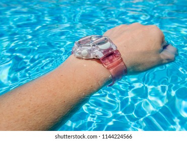 pink plastic digital waterproof watch on a wrist in an outside swimming pool