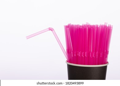 Pink plastic straws in black disposable paper cup isolated on white background. One flexible straw apart - uniqueness, nonconformism, protest concept. Cafe, cocktail party, drinks. Copy space close up