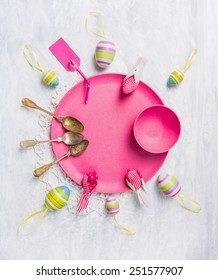 Pink plate with Easter eggs, spoons, ribbons and sign, top view