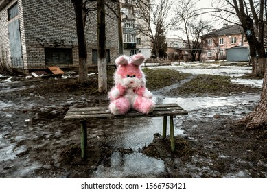 Pink plush rabbit sits on a bench in a poor residential area. Bad wheather. Deppresion. Sadness