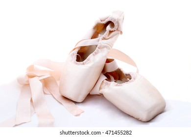 Pink pointe ballet shoes on white