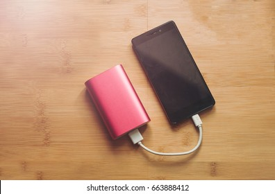 Pink powerbank charges smartphone
