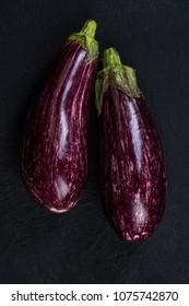 Pink or purple aubergine on dark slate.