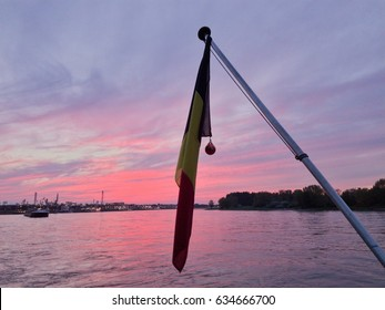pink purple clouds and a Belgium flag at the Rhine River