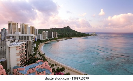 Pink and purple clouds reflect off the turquoise waters of Waikiki Beach in Oahu, Hawaii.