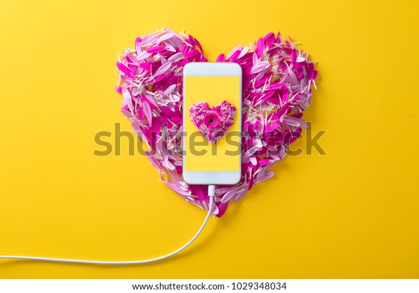 Pink and purple flower petals in heart shape and mobile phone on yellow background.