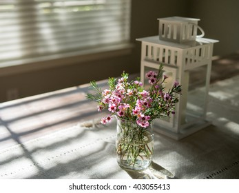 Pink and purple flowers glass vase on rustic table near window with sunlight shining through, top view