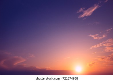 Pink and purple sunset against a background of clear sky and small clouds. Sunset composition