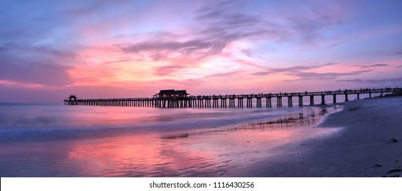 Pink and purple sunset over the Naples Pier in summer in Naples, Florida