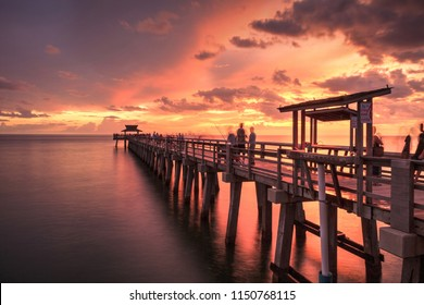 Pink and purple sunset over the Naples Pier on the Gulf Coast of Naples, Florida in summer.