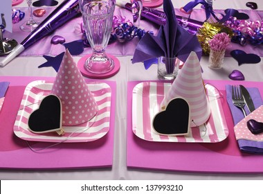 Pink and purple theme party table setting decorations, with polka dot and stripe pink party hats with heart shape blackboard blank message.