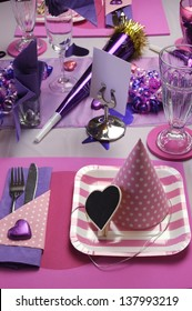 Pink and purple theme party table setting decoration, with party hat and plate table setting - vertical..