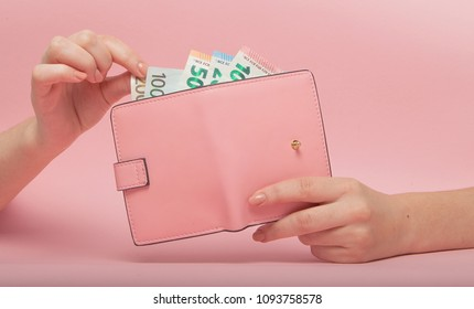 Pink purse and Euro banknotes in Female hands on pink background. Business Concept and Instagram.