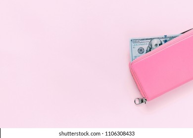 pink purse with hundred dollar banknotes on pink background. Flat lay, top view, copy space