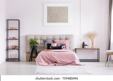 Pink quilt on bed with patterned pillows and copper lamp in stylish bedroom interior with metallic design