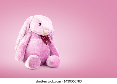 Pink rabbit doll with big ears on sweet background. Cute stuffed animal and fluffy fur for kids.