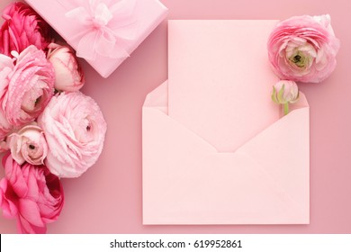 Pink ranunculus flowers, gift or present box and empty card with envelope on table. Mothers Day, Birthday, Valentines Day, Womens Day, celebration concept. Top view, flat lay.