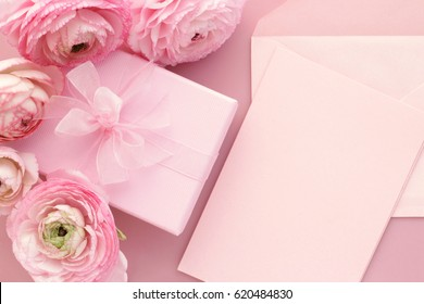 Pink ranunculus flowers, gift or present box and empty card with envelope on table. Mothers Day, Birthday, Valentines Day, Womens Day, celebration concept. Top view.