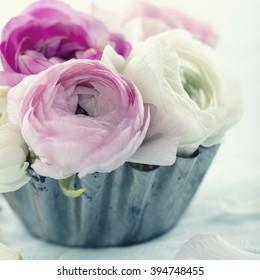 Pink ranunculus flowers in a metal tin cup