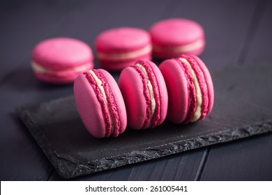 Pink raspberry macaroons on black wooden background