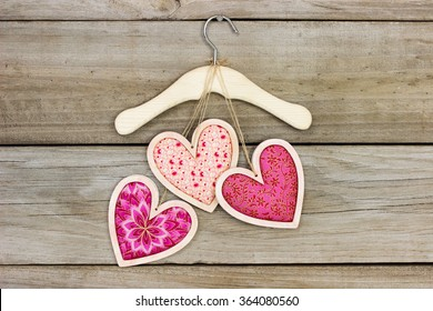 Pink and red country fabric hearts hanging by rope on hanger with antique rustic wood background; Valentine's Day and love concept with wooden copy space