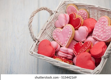 pink and red heart-shaped cookies in a square wicker basket close-up