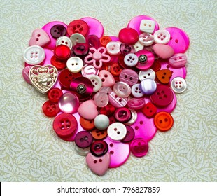 Pink, Red, and Purple Buttons in the shape of a Heart on a lace background