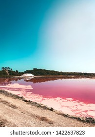 pink and red salt evaporation pond of a sea salt farm on a sunny summer day with blue sky. Visit on travel vacation.  Flor de sal d'es Trenc, Mallorca Spain