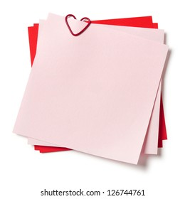 pink and red sticky notes with paper clip in shape of heart on white background