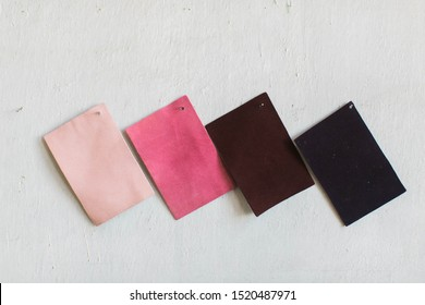 Pink and red suede leather cowhide swatches on white wall, copy space