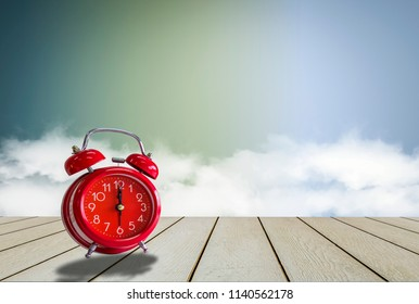Pink Retro Alarm Clock, wood table,  pale blue background. And fog and light, With concept of color, simplicity, relaxation and fun time walking forward, With copy space.