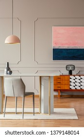Pink retro pendant light above a marble table in an eclectic dining room interior with wooden furniture and art