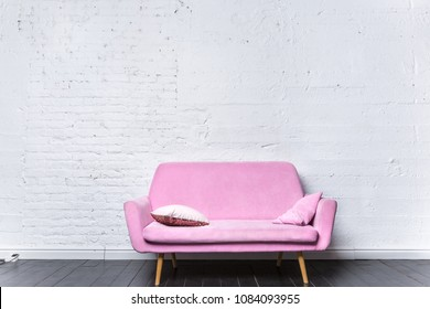 Pink retro sofa against white brick wall