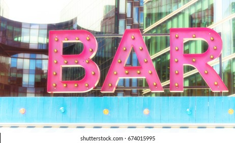 Pink retro styled bar sign in London, UK. Processed to look like a faded image from the 1950s or 60s.