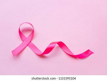 Pink ribbon, breast cancer awareness symbol on pink background.