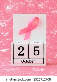 Pink ribbon of breast cancer awareness on a white wooden perpetual calendar with date 25 october. International breast cancer awareness month. Healthcare.