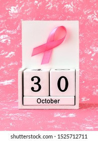 Pink ribbon of breast cancer awareness on a white wooden perpetual calendar with date 30 october. International breast cancer awareness month. Healthcare.