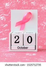 Pink ribbon of breast cancer awareness on a white wooden perpetual calendar with date 20 october. International breast cancer awareness month. Healthcare.