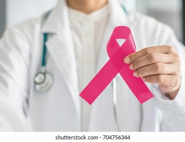 Pink ribbon for breast cancer awareness in doctor's hand, symbolic bow color for raising awareness charity campaign on women (female)  patient living with breast tumor illness