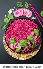 Pink rice (rice with beetroot juice) with radish and spinach leaves in a black plate on a dark background. Useful and beautiful food