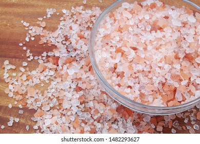Pink rock salt in bowl and on wooden table