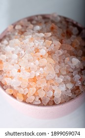 Pink rock salt in a pink bowl on a white background. Himalayan salt in bowl.