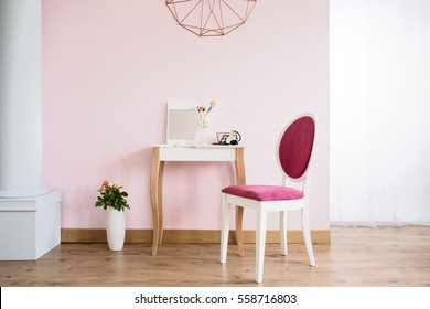 Pink room with column, dressing table and upholstered chair