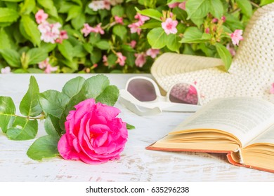 Pink rose, the book, white hat and sunglasses on the table in the summer garden in evening sunlight on a background of flowering weigela, close-up. Selective focus
