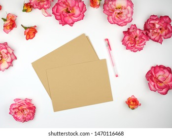 pink rose buds and a brown paper envelope on a white background, flat lay