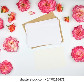 pink rose buds and a white paper envelope on a white background, top view, flat lay