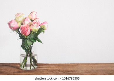Pink rose flowers in vase on wooden table with copy space