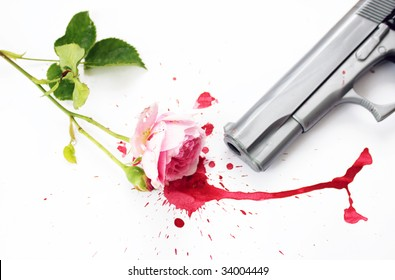 A pink rose with green stems and leaves, lying in a pool of red blood with the barrel of a gun visible. Set on a white background.
