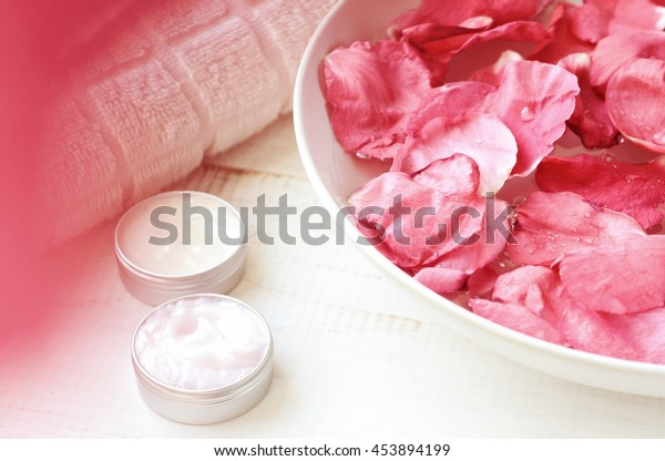 Pink rose petals in bowl, cosmetic moisturizer emollient in containers, white towel.  Pink natural blur, creamy tones. Fragrant rose flower spa. Natural herbal skincare.